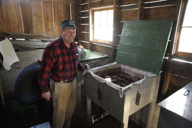 Haskell Yancey stands with syrup ready for canning, 2010.