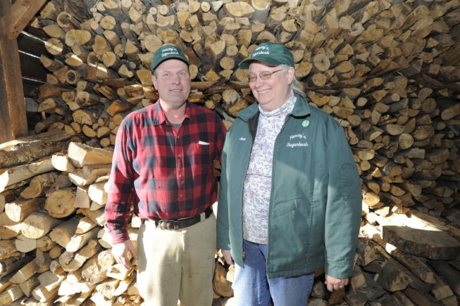 Haskell and Jane Yancey stand by the wood they'll use to fuel the operation's 1920s evaporator, 2010.