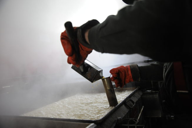 Gauging the sap being boiled into syrup in the evaporator, 2010.