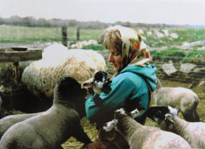 """This photo of Loretta's youngest sister Janet with her lambs was Loretta's reference for the """"Shepherdess"""" painting in her Family Farm portrait series project. Photographer unknown, c. 1980s. Courtesy of Loretta Lepkowski."""