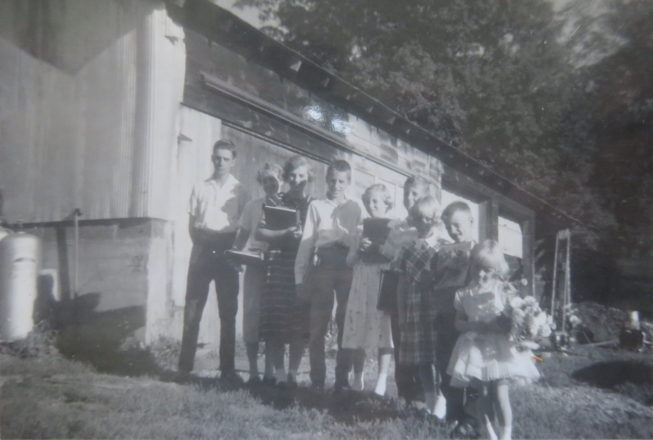 Loretta and siblings line up for school in front of the garage where they lived for nine years, the three youngest girls sharing a bed, while her parents rebuilt after a house fire at her family farm on Kentner Rd. near Constableville. NY. Photographer unknown, 1960. Courtesy of Loretta Lepkowski.