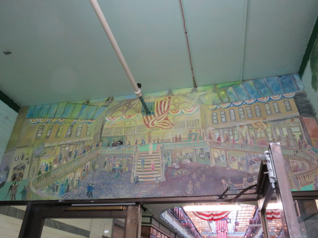 An entryway features a set of murals by local artist Ronald Collins, depicting themes from the Paddock Arcade's 19th-century days as a place for the fashionable to see and be seen, to the Watertown origins of the Woolworth's five-and-dime store chain, to the bustling Jefferson County Fair, celebrated locally as the oldest continually running fair in the country. Photo by  Camilla Ammirati, 2017.