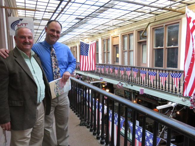 Steve Duffany, who is one of the longest-standing proprietors (as of 2017) with his insurance business in the Arcade, and Dr. Jason White, a local history buff and friend of the Paddock Arcade community, show visiting folklorists around the upper level during documentation for the award. Photo by Camilla Ammirati, 2017.
