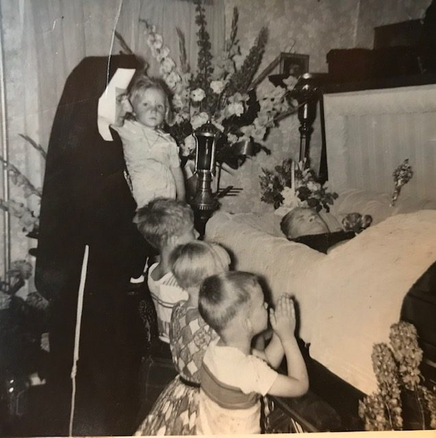 """Loretta (kneeling) and siblings with their aunt, Sister Regis, at their grandmother """"Babcah""""'s wake in her farm house in Westernville, NY. In keeping with local tradition, both Loretta's maternal grandparents' caskets were laid out in the parlor at home. Photographer unknown, 1958. Courtesy of Loretta Lepkowski."""