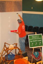 Tom Love, crew foreman for Continental Construction Company, is taping and filling dry wall before painting the temporary dust barrier on the main floor.